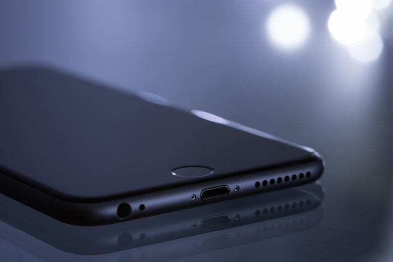 a black iphone sitting on a sheer surface, hexagonal lights in the background