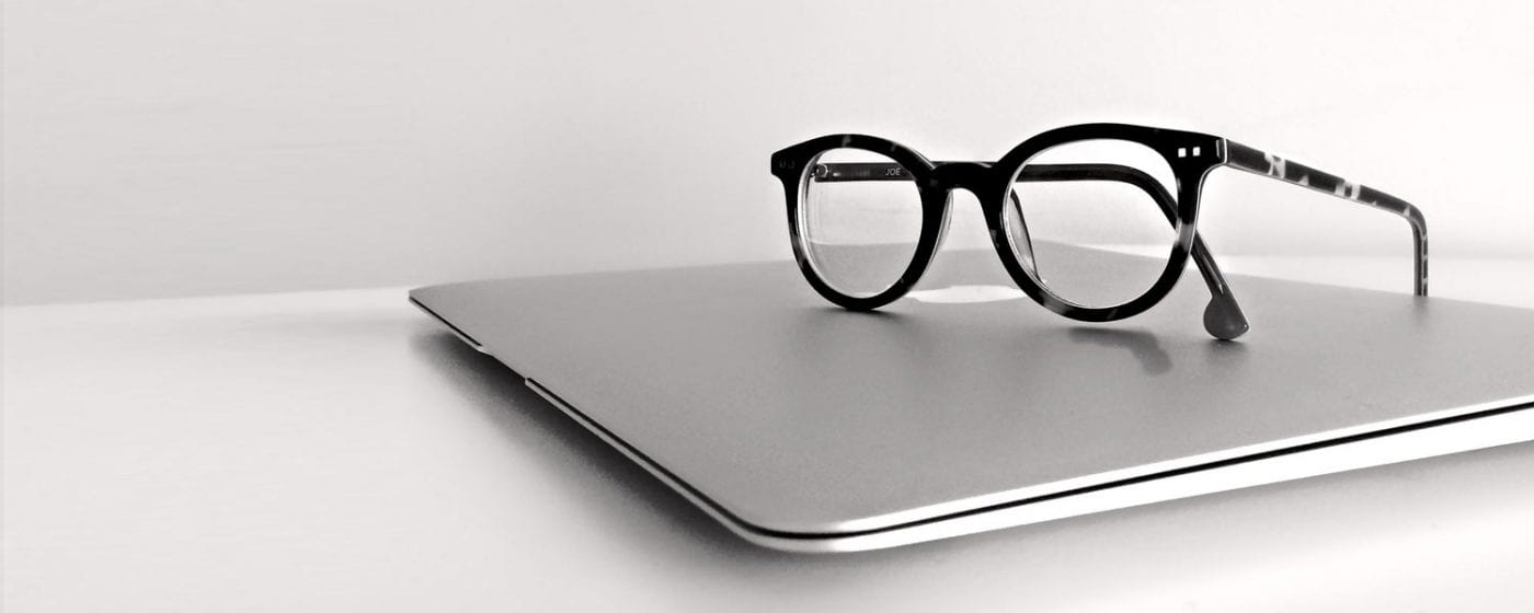 a pair of glasses sit atop a laptop that has been repaired to work like new again