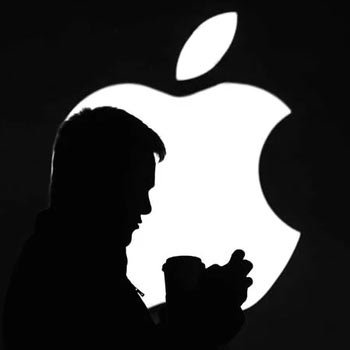 a silhouette stands in front of the apple logo